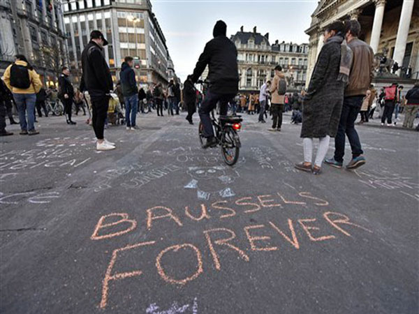 """A writing on the asphalt reads """"Brussels forever"""" at the place de la Bourse in the center of Brussels, where people write hundreds of messages on the ground to remember the victims of todays attack, Tuesday, March 22, 2016. Bombs exploded at the Brussels airport and one of the city's metro stations Tuesday, killing and wounding scores of people, as a European capital was again locked down amid heightened security threats. (AP Photo/Martin Meissner)"""