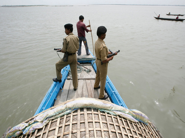 Indian Border Security Force (BSF) soldiers patrol on a boat in the waters of river Brahmaputra near the border with Bangladesh ahead of second phase polls, at Dhubri, about 280 km (174 miles) west from Guwahati, the major city of India's northeastern state of Assam April 22, 2009. India will hold a general election between April 16 and May 13. REUTERS/Rupak De Chowdhuri (INDIA MILITARY POLITICS ELECTIONS) - RTXE9BK